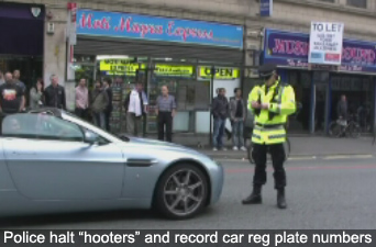 Police recording car registration plate numbers of passing motorists beeping their horns in support of protesters