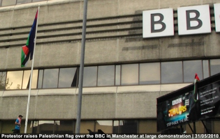 Palestinian flag is raised above the BBC in Manchester by a protester in solidarity with the flotilla carrying humanitarian relief to Gaza by Israeli forces
